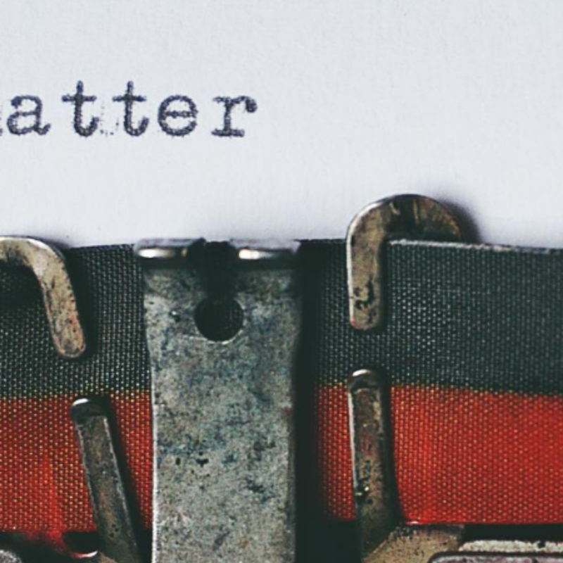 "Ribbon on a typewriter with the words ""stories matter"" above"