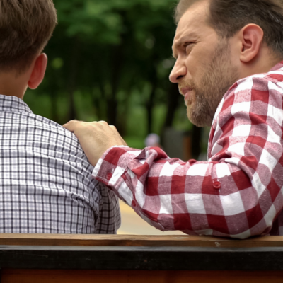 Dad putting hand on shoulder of teenage son to stay connected