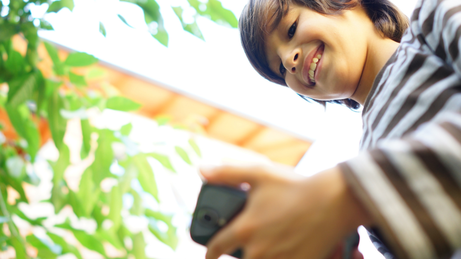 Teenager looking at his phone with a smile on his face, demonstrating good digital citizenship