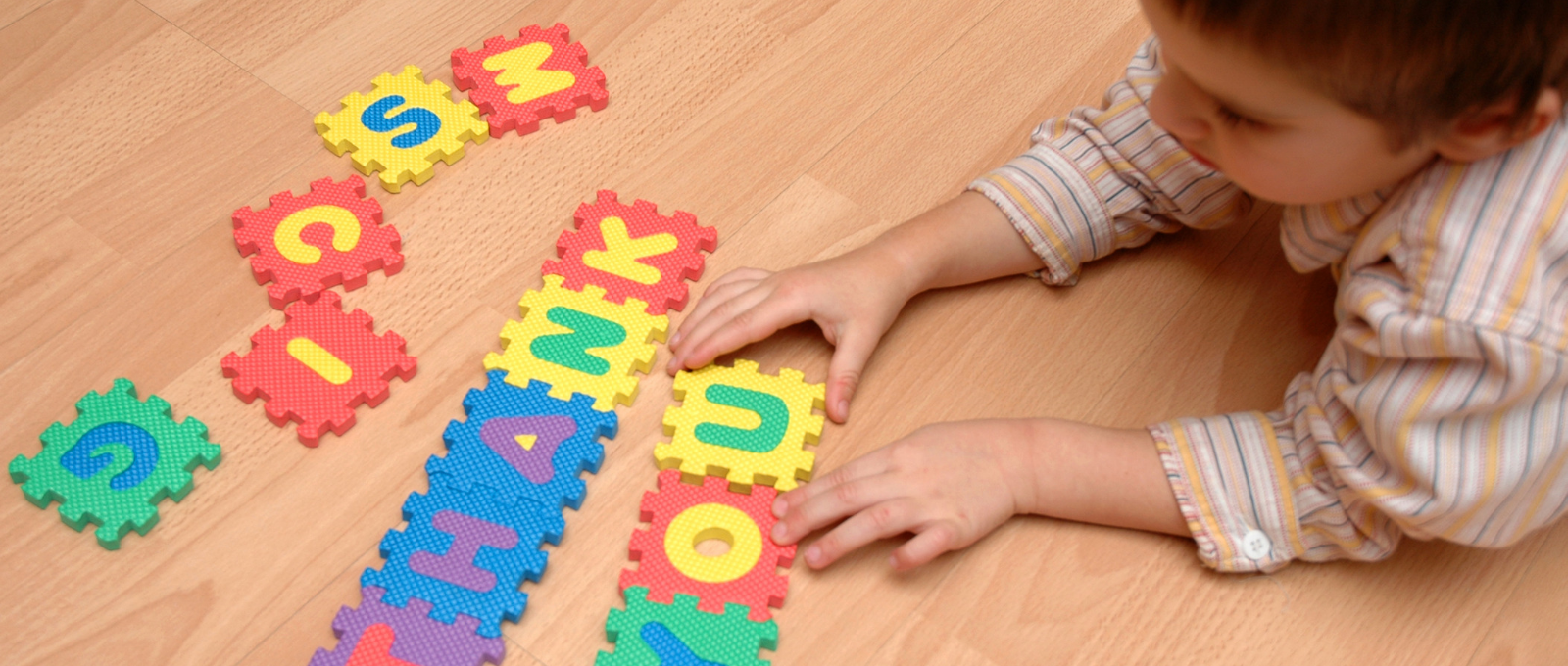 "Child playing with letters on floor that spell ""thank you"" symbolizing gratitude"