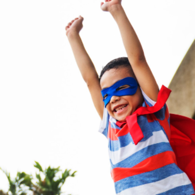 Child in superhero cape displaying courage