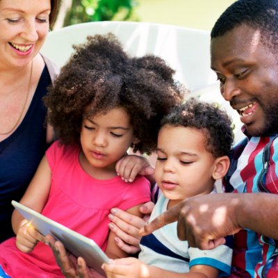 Two parents setting parental controls on a tablet with their two children.