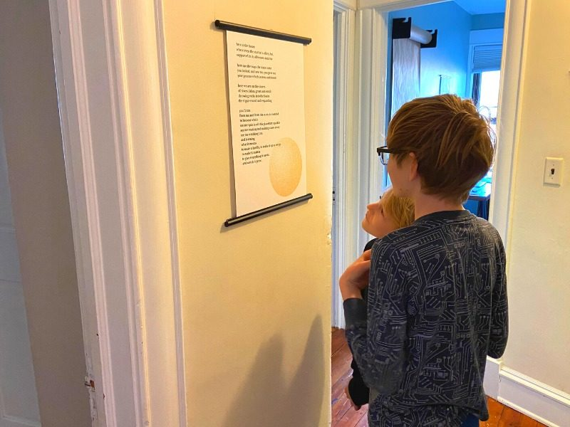 Two kids standing in the hallways reading their family poem