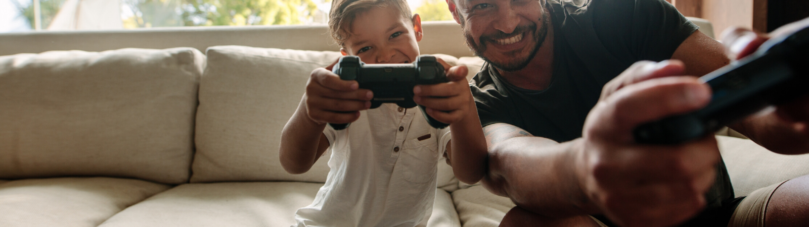 Dad and kid playing video games together on the couch
