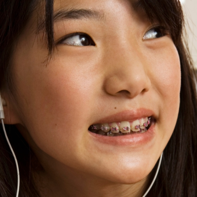 Teenage girl listening to podcast with earbuds.