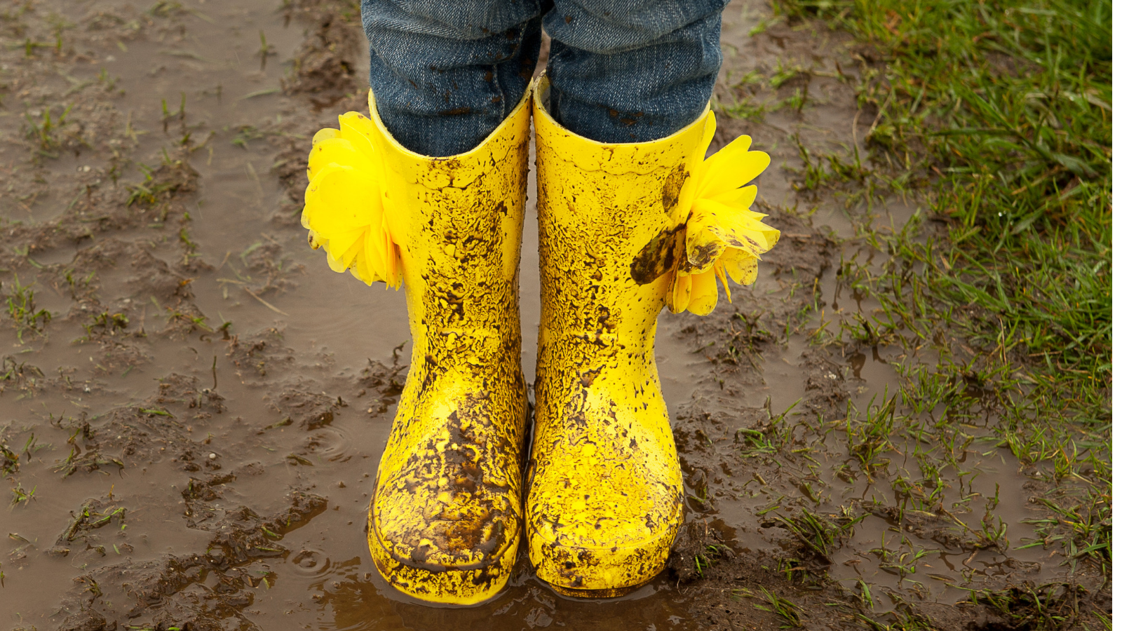Child's bright boots in muddy puddle indicating resilience