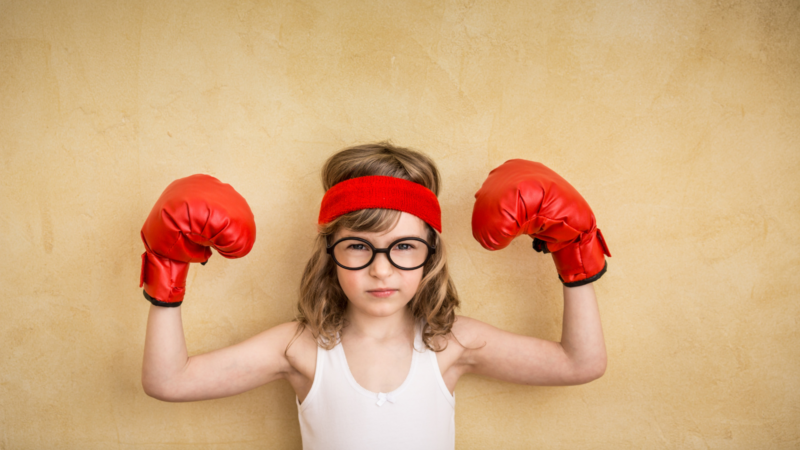 Child posing with strong muscles displaying growth mindset
