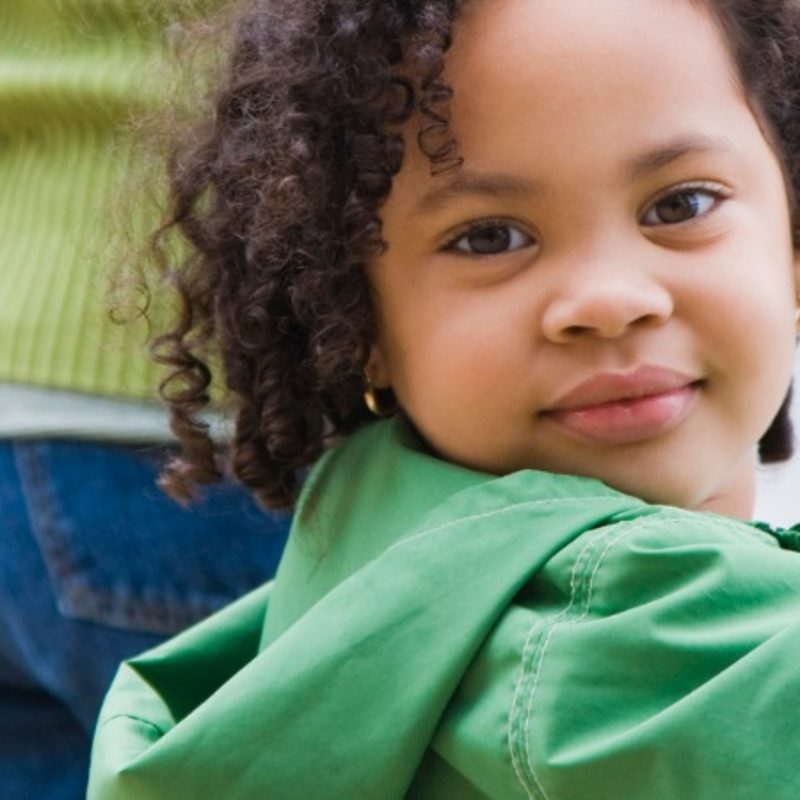 Young child with curly hair looking directly at camera while holding caregivers hands
