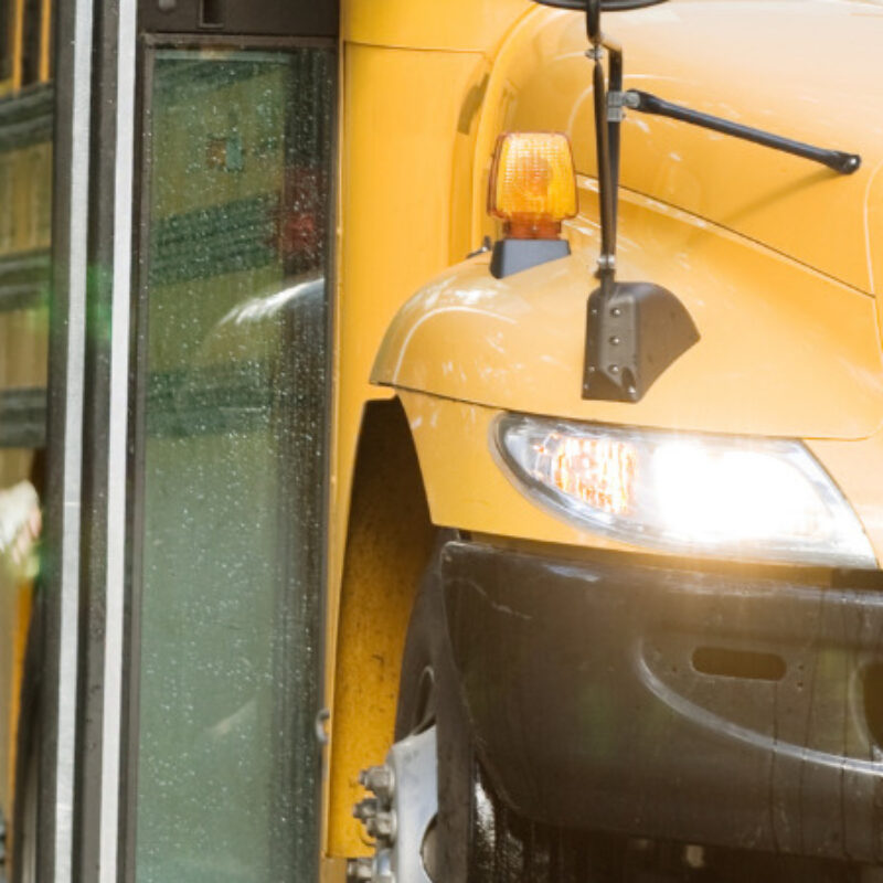 Child boarding school bus with a mask