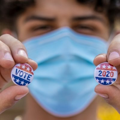 Masked teenager holding up two pins that say VOTE and 2020