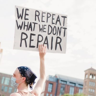 "Teenager with a mask holding a sign that says ""we repeat what we don't repair"""