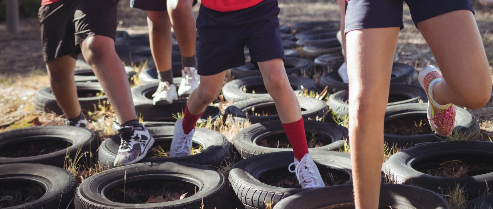 Children running through obstacles on ground.