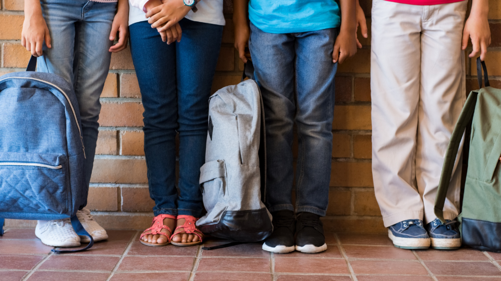 Four kids going back to school with their backpacks at their feet