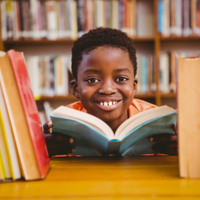 Child reading diverse books in a library