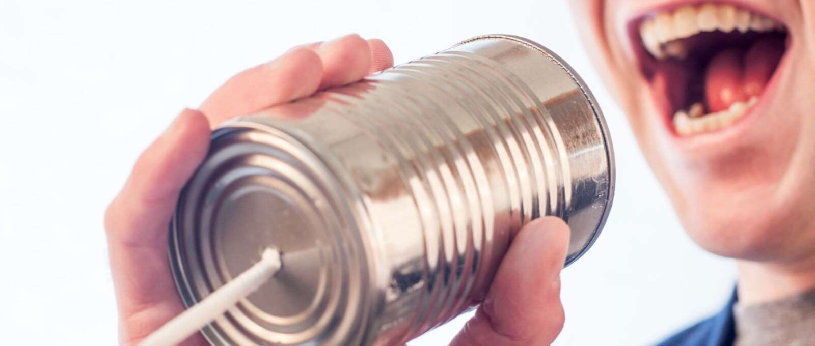 Person talking into tin can to symbolize communication