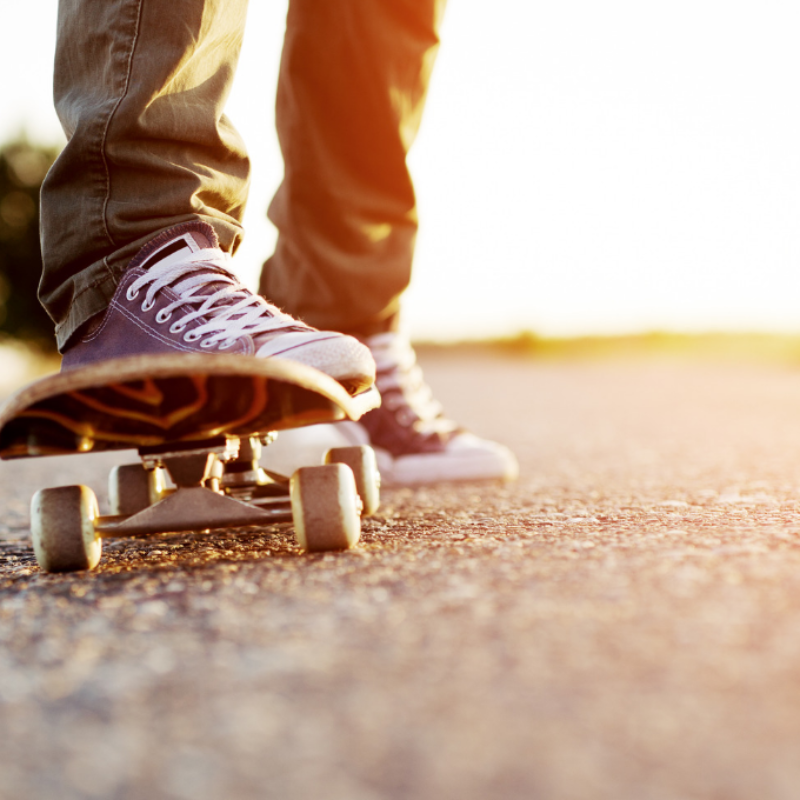 Feet of teenager standing on skateboard