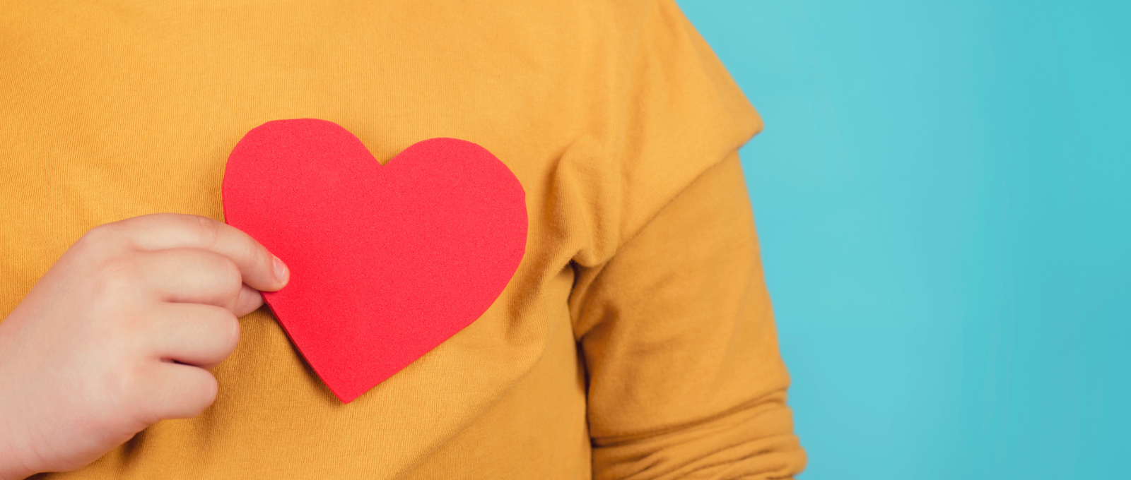 Person holding a heart over their chest to symbolize empathy
