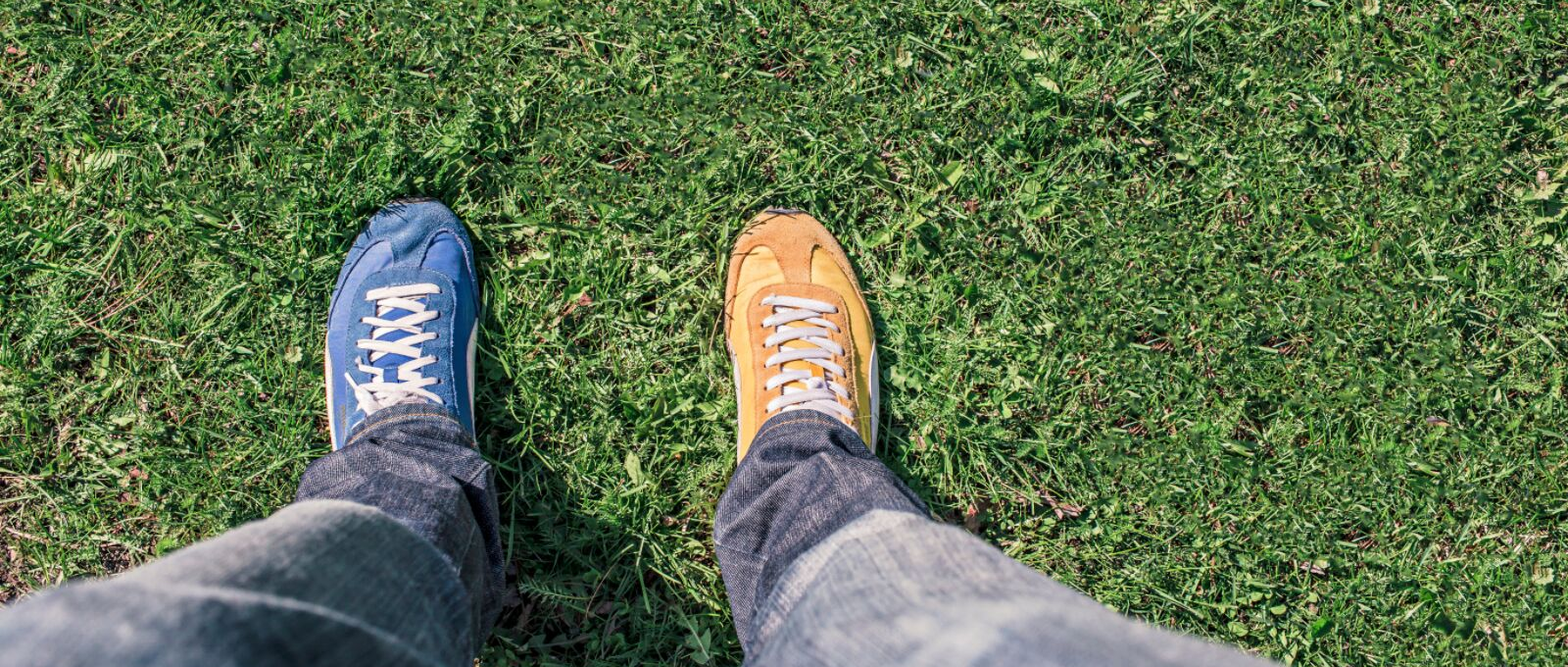 Looking down on two different color shoes to symbolize empathy, standing in someone else's shoes