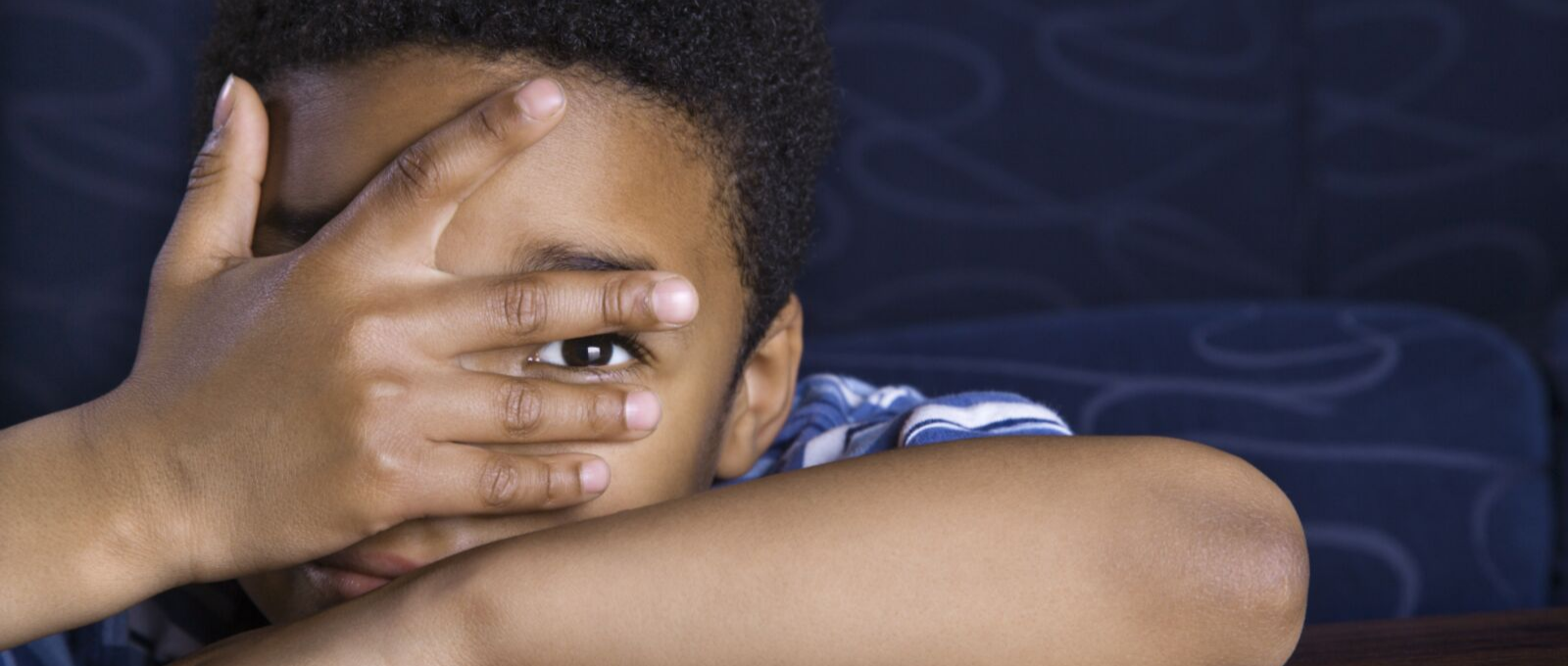 Child leaning on arms and looking through hands