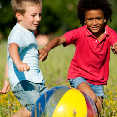 Three children engaged in free play in a field