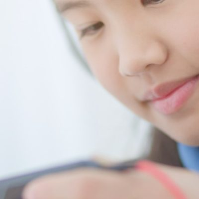 Teenager with headphones on looking at cell phone