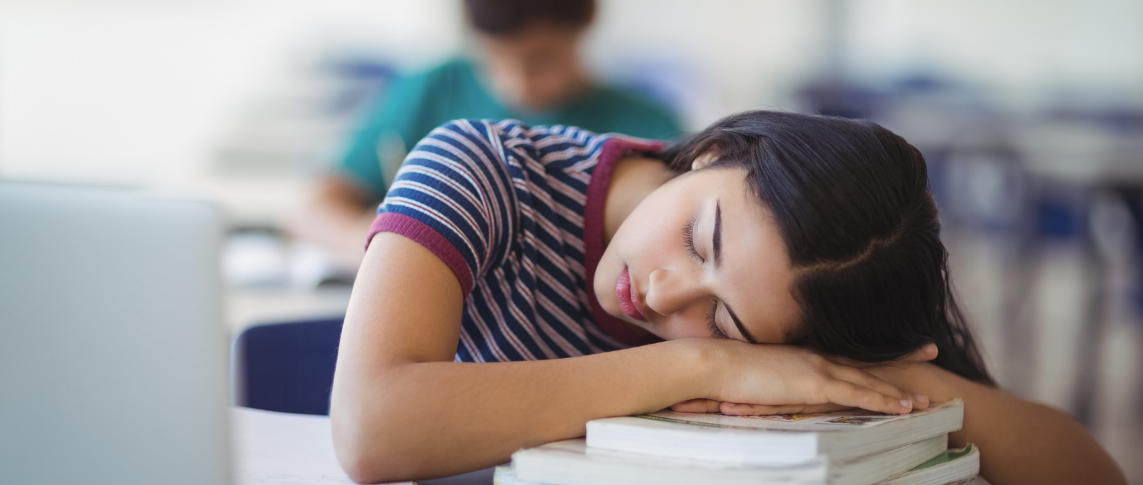 Teenager sleeping at desk on a pile of books at school