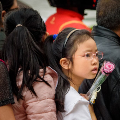 Child holding single pink rose in the wake of a tragedy like a mass shooting
