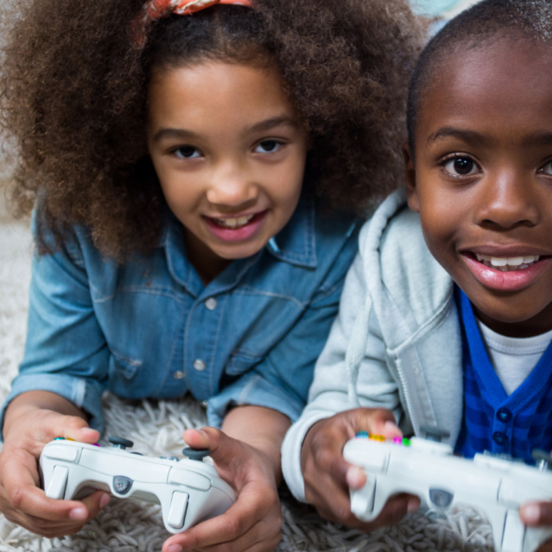 Two children laying on rug playing video games together.