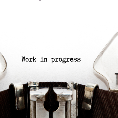 page coming out of typewriter that says Work In Progress